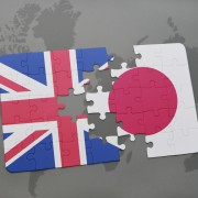 puzzle with the national flag of great britain and japan on a world map background.