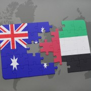 puzzle with the national flag of australia and united arab emirates on a world map background.